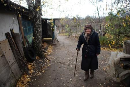 "An elderly woman is standing in the yard of her house (eastern Ukraine, GCA)""."